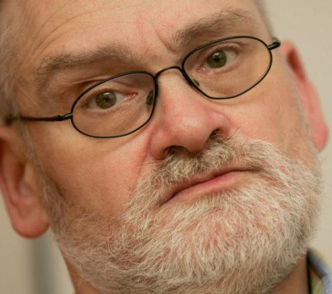 Sie sehen einen Mann mit Brille, grün-grauen Augen und grauem Vollbart mit schief gelegtem Kopf